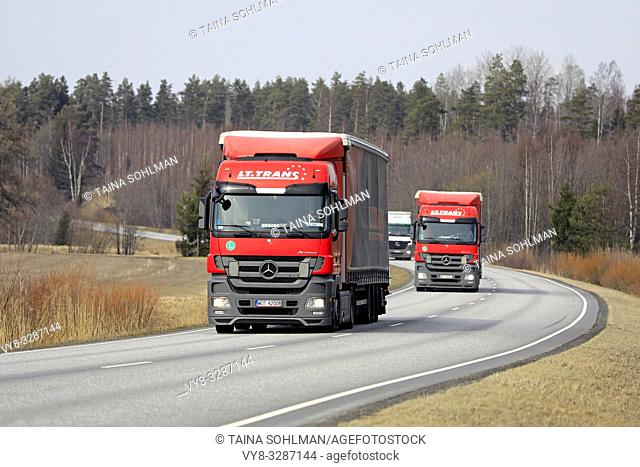 Salo, Finland - April 5, 2019: Fleet of Mercedes-Benz Actros semi trailer cargo trucks transporting goods along road in Finland on a day of spring
