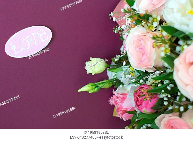 Wedding background. Delicate roses in a bouquet. Romantic postcard in pink and purple tones. Love lettering on a romantic background. Rose petals