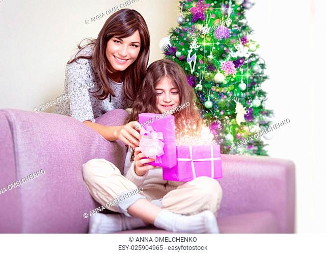 Cute teen girl receive gift from her beautiful young mother, happy family enjoying magical glowing present, spending Christmas holidays at home