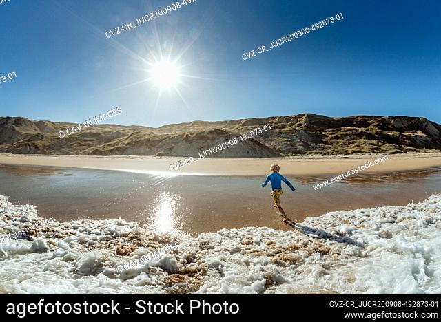 View from ocean of young child running from waves on a sunny day in New Zealand