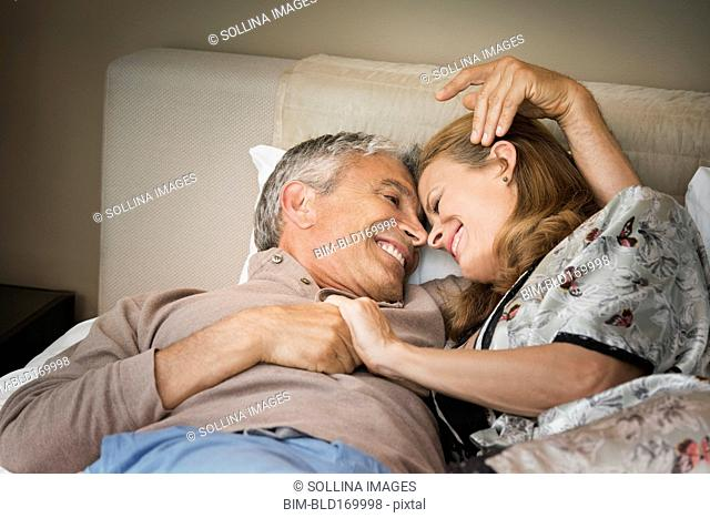 Laughing couple relaxing on bed