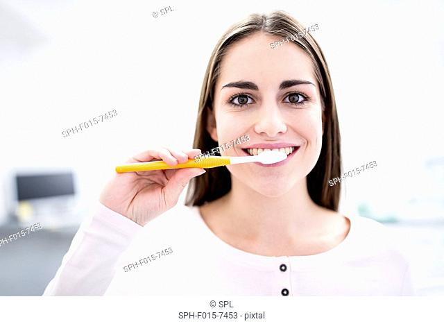 MODEL RELEASED. Young woman brushing teeth, portrait, close-up