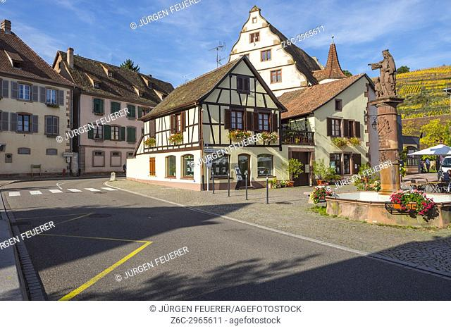 half-timbered houses with fountain and view to the vineyards in the village Andlau, foothills of the Vosges Mountains, on the Wine Route of Alsace, France