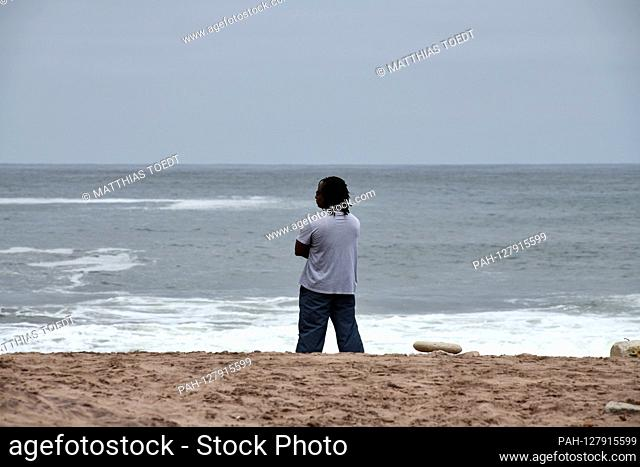 A man stands on the beach in the Namibian town of Swakopmund and looks out over the Atlantic Ocean, taken on 02.03.2019. Photo: Matthias Toedt / dpa-Zentralbild...