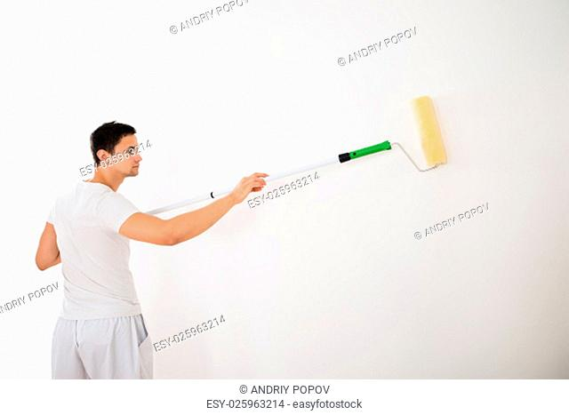 Side view of young man using paint roller on white wall at home