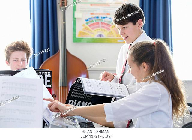 Highs school students playing piano with sheet music in music class