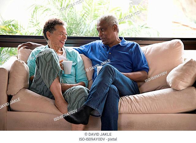 Senior couple sitting on sofa, drinking hot drink