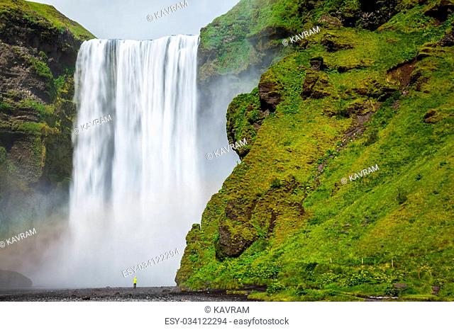 The most popular waterfall in Iceland - Skogafoss. Water rushes down with a crash, forming a cloud of mist. Picturesque huge rainbow appears in the water mist