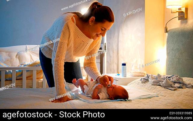 Young caring mother giving soother to her little baby boy crying on bed at night. Parent giving pacifier to newborn child
