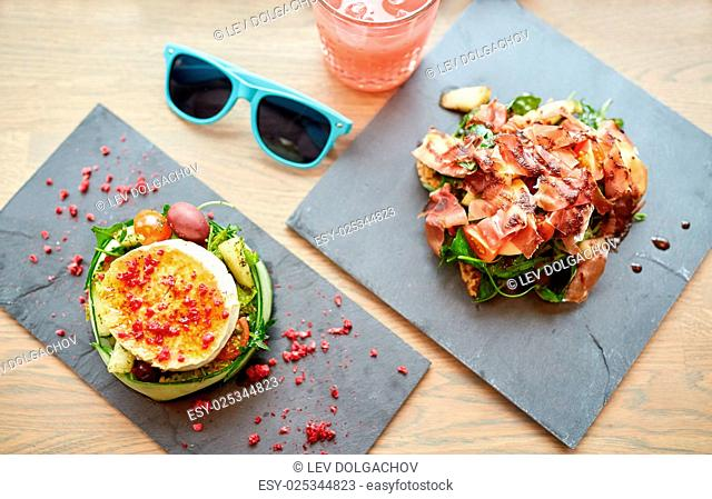 food, culinary, haute cuisine and cooking concept - goat cheese and prosciutto ham salads on stone plates with glass of juice and sunglasses on table at...
