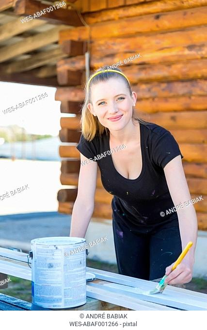 Smiling young woman painting bars