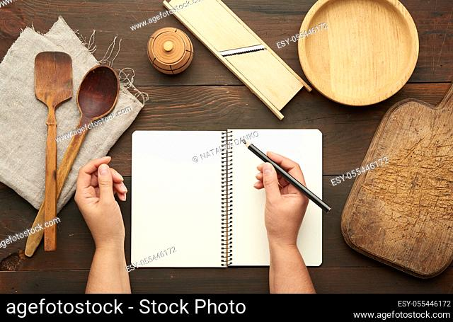 open notebook with blank white sheets and kitchen utensils on a brown wooden table, female hands hold a black pencil, top view