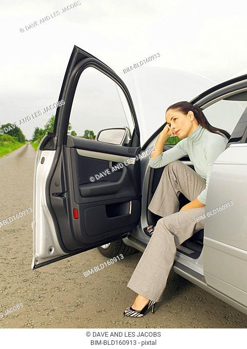 Caucasian businesswoman in broken down car on rural road