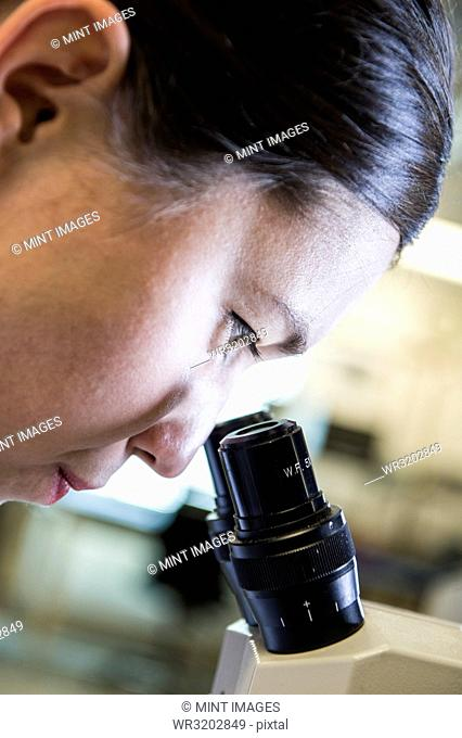 A Caucasian female technician using a microscope to examine a part in a technical research and development site