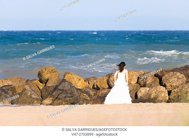 Woman dressed in wedding on the beach Cullera, Valencia, Spain, Europe