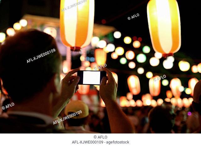 Caucasian man taking pictures at Japanese traditional Bon Odori festival