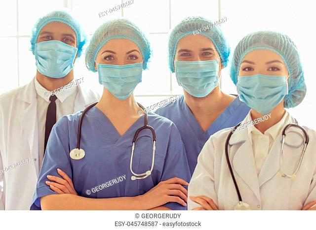 Medical doctors of different nationalities and genders in masks and caps are looking at camera and smiling, standing with crossed arms
