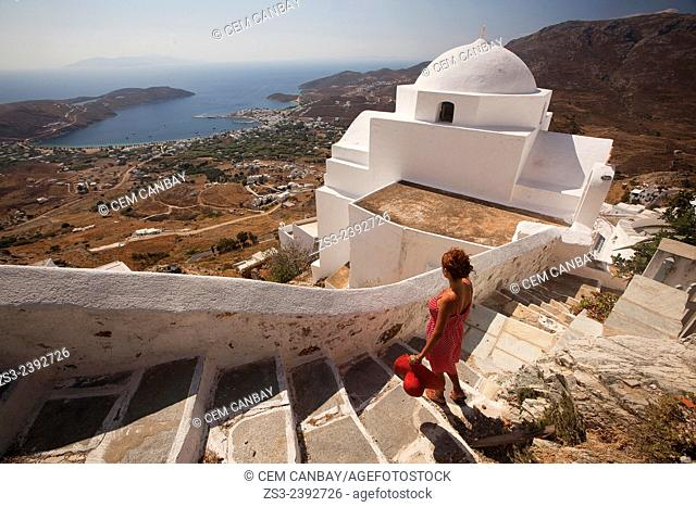 Woman looking down to the port from the stairs of a church in Hora, Serifos, Cyclades Islands, Greek Islands, Greece, Europe