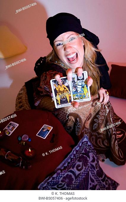 woman telling fortune out of tarot cards, showing dead and devil
