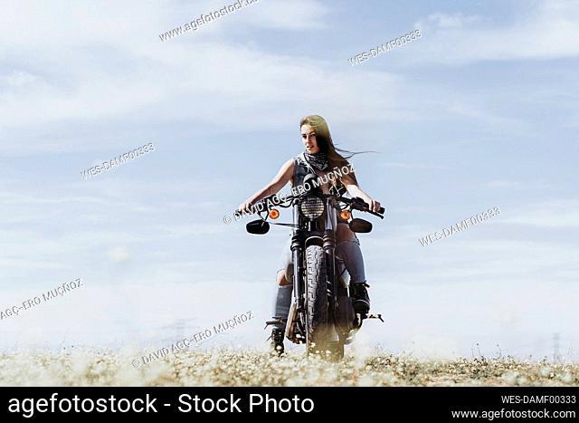 Young beautiful woman riding motorbike