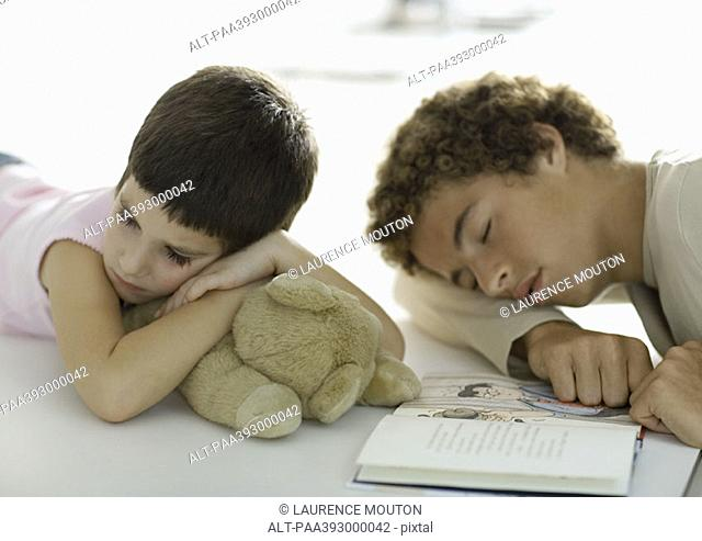 Adolescent boy and younger sibling falling asleep while reading book