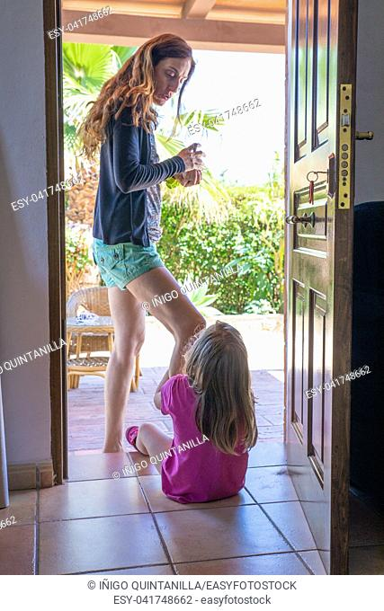 woman mother standing with a cup in hands talking to her daughter, four years old blonde girl, sitting in doorway of a house, in Summertime