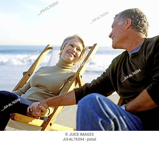 View of a couple holding hands in lawn chairs on the beach