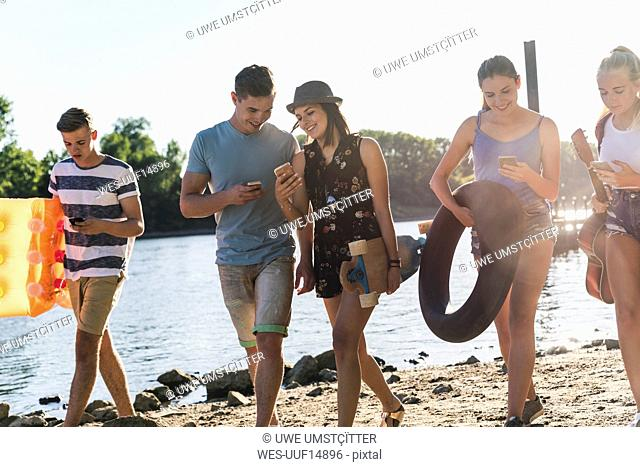Group of friends with cell phones walking at the riverside