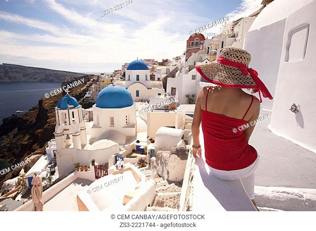 Woman in front of the blue domed church in Oia town looking at Caldera, Santorini, Cyclades Islands, Greek Islands, Greece, Europe