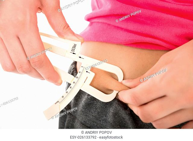 Midsection of young woman measuring fats with caliper against white background