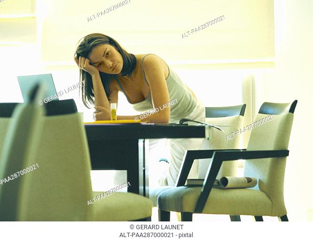Female telecommuter leaning on table