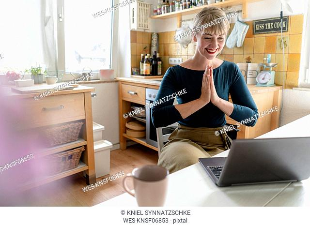 Portrait of laughing woman with laptop practicing yoga in the kitchen