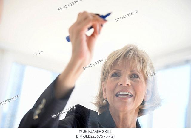 Caucasian businesswoman writing on glass wall