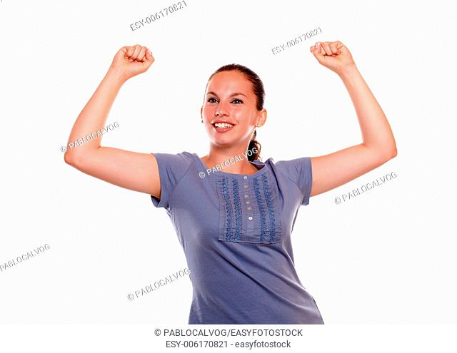 Excited young woman smiling with hands up on blue shirt on white background