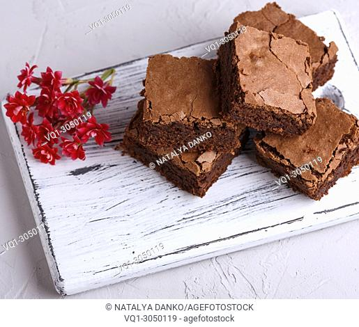 stack of square pieces of brownie on a white wooden board, top view