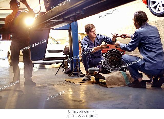 Mechanics discussing part in auto repair shop