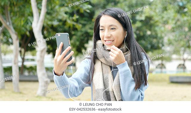 Woman making a video call on cellphone at outdoor