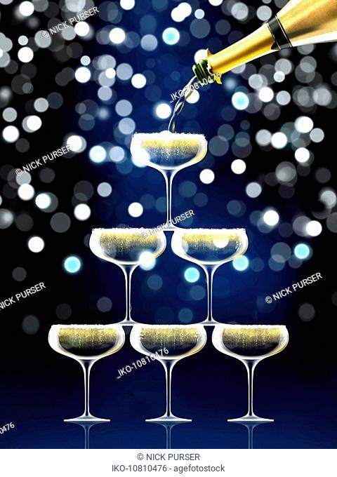 Champagne bottle filling coupe glasses in sparkling champagne pyramid