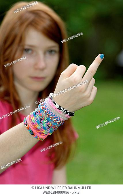 Girl with looms at her wrist giving the finger