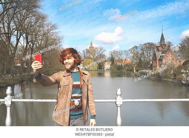 Belgium, Bruges, young man taking a selfie at Minnewater