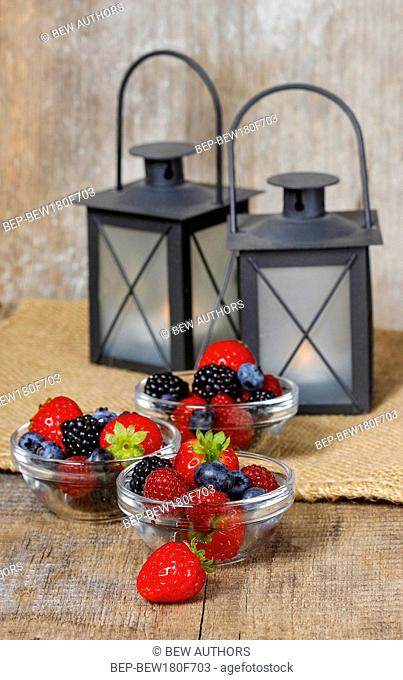 Fruit salad in small bowls on wooden table. Black iron lanterns in the background. Summer holiday healthy dessert. Garden party setting