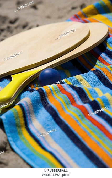 Close-up of paddleball rackets and ball on a towel