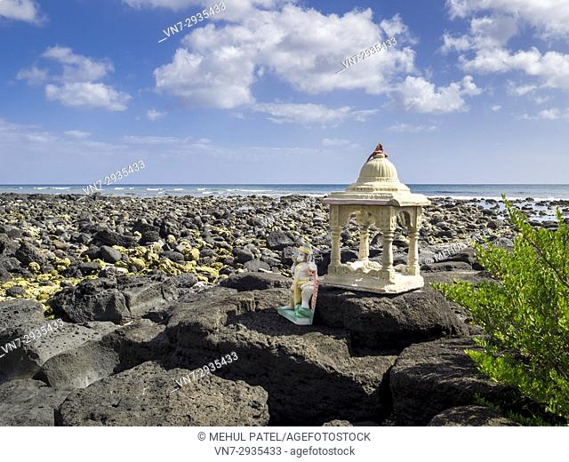 Shrine and statue of Hindu deity Lord Hanuman on rocks by sea, Pointe aux Piments, Mauritius