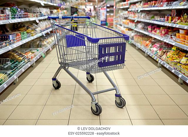 consumerism concept - empty shopping cart or trolley at supermarket