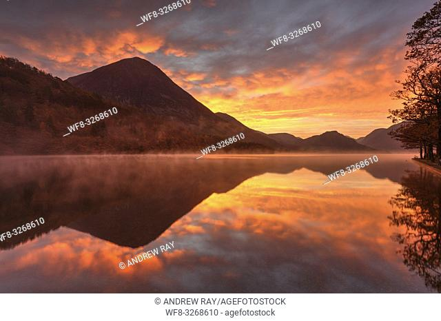 A spectacular sunrise captured from the northern end of Crummock Water in the Lake District National Park, on a still misty morning in late October