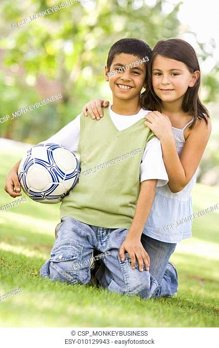Children playing football in park