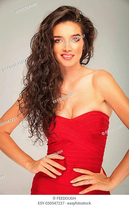 busty model in red dress touching her waist while posing and smiling at the camera