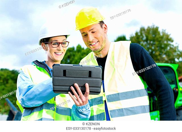 Construction worker and engineer on site discussing blueprints on pad or tablet computer, excavator and other construction machinery in background