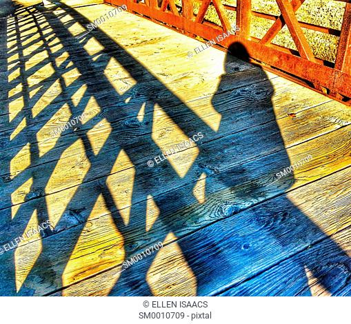 Shadow of a person walking across an iron bridge with strong shadows cast on the wooden planks of the bridge