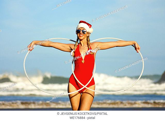 Happy girl in red bikini and christmas hat standing on the beach with two white hula hoops